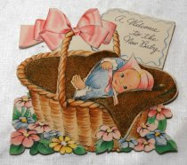 Image of 2017.008.031.1.5 - Baby Greeting Card to JoAnn Semones, 1945. Image on the card depicts a baby, in a blue outfit and pink bonnet, in a wicker basket with a pink bow and wrapped in a brown blanket in a field of yellow, pink, and blue flowers. The texture of the blanket is felt. The card is cut in the shape of the front cover image. There is a tag on the wicker basket. On the inside cover, is a drawing of a pin bonnet with blue ribbons and pink and blue shoes.