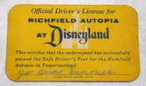 Image of 2017.008.042.5 - Disneyland Driver's License, 1955. Business-card-sized rectangular paper with rounded corners. The background is yellow and the printed text, stating that the cardholder is licensed to drive in Disneyland's Richfield Autopia, is dark blue. On the front behind the text is a white castle. Jo Ann Semones's name is signed in pencil at the bottom. On the back, her age, height, weight, and eye and hair colors are also filled in in pencil, as though it was a real driver's license.