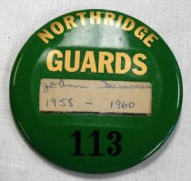 """Image of 2017.008.043.25 - Northridge Guards Button, c. 1958-1960. Green plastic circular button with a black metal backing. At the top of the button is printed """"NORTHRIDGE GUARDS"""" in gold; at the bottom is """"113"""" in black. Just below the center of the button is a clear rectangular cutout, into which is inserted an off-white piece of paper with """"JoAnn Semones 1958-1960"""" handwritten in cursive in blue pen. The back of the pin has a brass-colored C-style clasp. The side that is glued to the pin is curved into a wave shape while the pin itself is straight."""