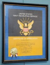 Image of 2017.008.046.4 - Framed US Navy Certificate of Appreciation, 1970. Framed certificate from the US Navy Recruiting Service awarded to JoAnn Semones. The top half of the certificate is black with a large gold eagle holding a red, white, and blue shield and and a ship's anchor. The bottom half is gold and contains black and white printed text stating the purpose of the award, the date and place of issue, and the signature of the district's commanding officer. In the bottom left corner is attached a gold foil seal with short red, white, and blue ribbons. The certificate is attached to a dark blue piece of paper that forms a border around it. The frame is wood, painted black with a narrow gold inside border. The back is plain faded bluish paper and has a metal hook at the top.