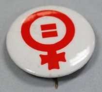Image of 2017.008.048.12 - ERA Button, c. 1970-1975. Circular plastic and metal button, with a red female/Venus symbol on a white background. Symbol consists of a circle with a small cross extending from it at the bottom. Inside the circle are two stacked horizontal dashes forming the equals sign. Back of the button has a vertical metal pin attached at the top with its tip extending slightly past the outside of the circle.