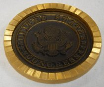 Image of 2017.008.048.4 - Congress Paperweight, c. 1970-1975. Circular paperweight with a dark bronze metal US Congress seal in the center and a gold border surrounding it. The border is gently ridged and resembles a sunburst when light reflects off of it. The text and eagle on the seal are raised, in relief, and the seal is set into the paperweight so the border is raised around it. It is set somewhat unevenly, so the top right part of the seal is deeper below the border, while the bottom left part is closer to the border's elevation. On the back is a black and slightly fuzzy backing.