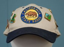 Image of 2017.008.059.10 - CA State Parks Cap, c. 2010-2016. CA State Parks Cap. Navy blue and pale taupe fabric baseball cap. On the front panel of the cap, there is an embroidered patch in the design and shape of the CA State Parks seal in gold and navy blue. The front and side panels are adorned with various colored pins: California State Parks volunteer appreciation, Ano Nuevo State Park Docent 2011 and 2012,  Railroad Museum, Seacliff, Asilomar Centennial, Mission Santa Cruz, Hearst Castle, California Coastal Monument, a bird pin, a red California pin, and a 2014 California State Parks Volunteer pin. On the back of the cap is an adjustable tuck strap with side closure.