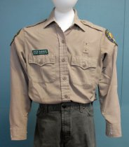 Image of 2017.008.060.2 - CA State Parks Shirt, c. 1999-2016. Khaki polyester/rayon button-down collared shirt. Has two buttoned chest pockets and a small rectangular patch with two vent holes above the proper left pocket. On the proper right chest is a green and white plastic name tag. On each sleeve at the shoulders is a circular patch with the California State Parks seal. Shirt has two shoulder straps extending from the top of the sleeve to button near the collar. Vertical darts run along the front and back. Buttons are plastic and khaki-colored. Sleeves have a reinforced patch along the forearms. There is a small tag below the collar's liner that has faded to the point of being illegible, and a main still legible tag below that.