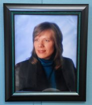 Image of 2017.008.061.1 - Framed Portrait Photograph of Julie Barrow, c. 1990-2003. Head and shoulders portrait photo of Julie Barrow against a blue-gray background. She wears a teal turtleneck and black blazer. Her hair is light brown and extends just past her shoulders. Her face is in 3/4 view with her gaze focused on something to the photographer's left. The frame is black wood with a matte finish, and inlaid along its inside edges is a narrow strip of teal-stained wood which forms an additional border close to the photo. On the back is a tan paper backing with a horizontal wire near the top, attached to the frame by metal hooks and screws, and two felt circles glued to the bottom corners. A white business card for Peggy Eriksen Gallery is also glued to the back at the bottom.