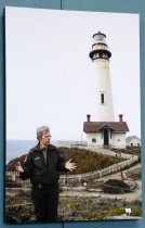 Image of 2017.008.061.2 - Mounted Photograph of Julie Barrow at Pigeon Point Lighthouse, c. 2007-2016. Color photograph in portrait orientation depicts Julie Barrow in the bottom left foreground and Pigeon Point Lighthouse in the right background. Barrow has short gray hair and glasses, and wears dark green pants and jacket over a button-up khaki shirt. She looks toward her left and spreads her hands as though giving a talk. The lighthouse is white with black details around the light and railings, a single narrow window about halfway up, and an attached small building with a red-brown roof and two chimneys. The ocean is visible behind Barrow, and the sky is an overcast white. The photo is mounted on a lightweight black plastic backing. The back has four indentations, presumably to attach a hanging mechanism, forming a diamond shape.
