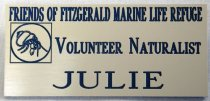Image of 2017.008.068.23 - Volunteer Name Tag, c. 1995-2007. Plastic name tag with an off-white front layer and a dark blue main layer for Julie Barrow, volunteer naturalist for the Friends of Fitzgerald Marine Life Refuge. The refuge name, volunteer title, and Julie's first name are cut out of the off-white layer to reveal the blue underneath. At the left side of the name tag is a logo of a hermit crab inside a circle which is then inside a square, with the edges of the circle touching the square in the middle of each side. This logo has also been cut out of the white plastic to show the blue underneath. On the back is a glued-on strip of clear plastic with two gold earring-style pins and backings, and a black and gold sticker for Lindeburg Jewelers in San Carlos.