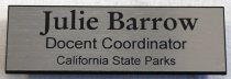 Image of 2017.008.068.24 - Docent Coordinator Name Tag, c. 2007-2016. Black and silver plastic name tag for Julie Barrow, giving her title as Docent Coordinator for California State Parks. The name tag is mostly black plastic, with a thin layer of silver plastic on the front. This plastic is shiny and has faint horizontal streaks across it to mimic metal. The text is cut out of this silver layer to reveal the black plastic below. On the back of the name tag is a silver metal bar; another silver bar with two strong magnets attached serves as the way to attach the name tag to clothing. Below the magnetic bar is a white sticker for Brinks Awards & Signs, in Santa Cruz.