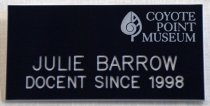 """Image of 2017.008.068.25 - Coyote Point Docent Badge, c. 1999-2016. Navy blue plastic name tag for Julie Barrow from the Coyote Point Museum. The museum's name and logo of a leaf with a spiral in its center are printed in pale blue at the top right corner. Julie's full name and """"DOCENT SINCE 1998"""" is engraved in larger white text across the bottom. On the back of the name tag, at the top, is a silver metal latching pin closure and a white sticker for """"RECOGNITION EXPRESS"""" in San Mateo."""