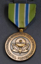 """Image of 2017.008.079.7 - EPA Bronze Medal, 1987. Awarded to Julie Barrow for commendable service with the Environmental Protection Agency. Medal (A) is circular and bronze; """"UNITED STATES ENVIRONMENTAL PROTECTION AGENCY"""" is written around the edge in raised text; and in the center is a design with a stylized butterfly on the bottom and a circle on top containing what looks like ocean waves and a smaller, raised circle near its center. The design is put together so it also looks like a stylized flower, with the butterfly being the stem and leaves and the circle the bulb. On the back is written """"FOR COMMENDABLE SERVICE"""" with her name and the year engraved underneath, surrounded by a leafy wreath pattern. Attached to the medal is a green ribbon with two vertical blue stripes bordered in white. Pin (B) is a smaller version of the medal, with the same border text and the same butterfly/flower design in the center. Box (C) is a soft vinyl, navy blue with a vertical painted gold design stripe on the left of the lid; the design is made up of two vertical stripes on either side and a pattern of alternating stylized plant designs in the center. The inside is lined in white papery vinyl and the medal and pin rest on a soft gray insert in the bottom of the box."""