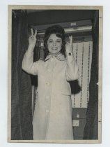 Image of 2017.054.002.38 - Untitled [Shirley Temple Black in front of a voting booth], March 2, 1971