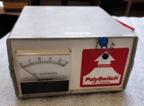 """Image of 2016.015.002.61 - Raychem Corporation PolySwitch Demo Unit, c. 1970s. Original device produced by the Raychem Corporation to demonstrate PolySwitch, an overcurrent circuit protection product (resettable fuse). The top and bottom of the rectangular case are gray plastic and with off-white plastic front and back panels. The case is fastened on the bottom with two screws. The front of the case has a red graphic of an arrow at right with the text, """"Raychem  /  PolySwitch  /  PTC Protection."""" A red light bulb appears within the arrow's point at upper right. A loop of wire with a circular enamel piece at center is set into the case above the top of the arrow. This component is the PolySwitch device. A black and white DC Amperes meter is set into the front side at left. The back of the case has a 13"""" red plastic tube with a 1/4"""" diameter attached with metal hardware at upper right and a small black switch at upper left. A 1/8"""" plug appears below the switch. The case rests on four cylindrical rubber feet."""