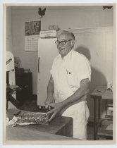 Image of 2017.054.004.6 - Untitled [Photograph of Fred Borchers cutting a piece of meat], June 19, 1986