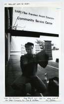 Image of 2017.054.005.2 - Untitled [Photograph of Greg Bosch putting up signs in front of door at BART door], n.d
