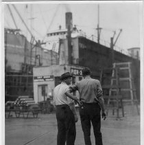 Image of B+W photo of two men, probably supervisors, near head of Pier 3, at Bethlehem Steel Shipyard, Hoboken Division, no date, ca. 1940. - Print, photographic