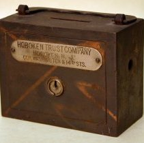 """Image of Steel bank with handle and coin slot with a plate that reads """" Hoboken Trust Company, Hoboken, N.J., corner Washington and 14th Streets.""""- - Box, Safe Deposit"""