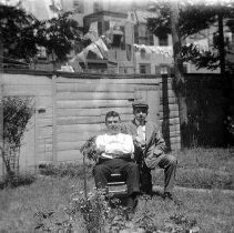 Image of B+W negative image of an unidentified man and a teen boy seated in a backyard, no place, no date, ca. 190 - Negative, Film