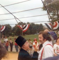 Image of Color photo of a player and an umpire 'arguing' in period costume on the field at Baseball Day Ceremonies, 1976. - Print, Photographic