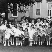 Image of B+W  group photo of of Hoboken Girl Scouts with flags standing in street, Hoboken, no date, ca. 1980-1985. - Print, Photographic