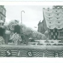 Image of B+W photo of the Tootsie Roll float in Hoboken Centennial celebration parade on Washington St. near 1st St. in Hoboken, 1955. - Print, Photographic