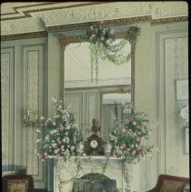 Image of Lantern slide, color, of a room with floral arrangements on a mantle, used for promotional display in Hoboken, no date, ca. 1920. - Transparency, Lantern-slide