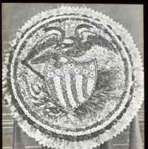 Image of Lantern slide, b+w, of floral decoration with eagle and patriotic shield motif, used for promotional display in Hoboken, no date, ca. 1920. - Transparency, Lantern-slide