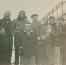 """Image of B+W group photo of """"On the Waterfront"""" filming in Hoboken: Marlon Brando is third from the left. Others are unidentified. No date, ca. Nov-Dec. 1953. - Print, photographic"""
