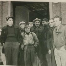 """Image of B+W group photo of """"On the Waterfront"""" filming in Hoboken: group of ten men near large building opening, Hoboken, no date, ca. late 1953-early 1954. - Print, photographic"""