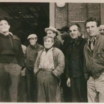 """Image of B+W group photo of """"On the Waterfront"""" filming in Hoboken: group of seven men near large building opening, Hoboken, no date, ca. late 1953-early 1954. - Print, photographic"""