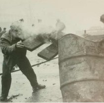 """Image of B+W photo of """"On the Waterfront"""" filming in Hoboken: an unidentified man near smoking metal barrel, Hoboken, n.d., ca. late 1953-early 1954. - Print, photographic"""