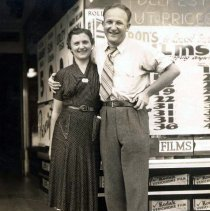 Image of B+W photo of a woman and man posed in front of the exterior of Baron's Drugstore, Hoboken, 1939. - Print, Photographic