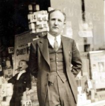Image of Sepia-tone photo of a man posed in front of the exterior of Baron's Drugstore, Hoboken, 1939. - Print, Photographic