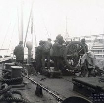 Image of Sepia-tone photo of men working on the deck of an unidentified vessel believed to be docked at the Hoboken piers, Hoboken?, no date, ca. 1916-1918. - Print, Photographic