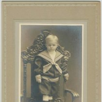 Image of B+W photo of young boy in sailor suit standing on chair, no date (ca. 1900). - Print, photographic