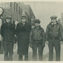 Image of B+W photo of 4 men posed in the winter in front of the Model Garage, 214 Clinton St., Hoboken, no date, ca. 1927. - Print, Photographic