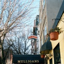 Image of Color photo of hanging sign for Hoboken Furniture, 157 First St. and a canvas marquee for Mulligans Bar, 159 First St.,  Hoboken, Jan. 3 & 4, 2002 - Print, Photographic