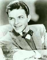 Image of Black-and-white photo of a young Frank Sinatra in a suit with sweater vest and bowtie, no place, no date, ca. 1939. - Print, Photographic