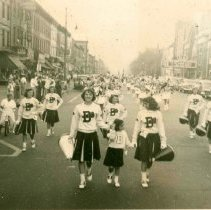 Image of B+W photo of A.J. Demarest High School cheerleaders and band marching on Washington St. after winning a football game, Hoboken, 1950. - Print, Photographic