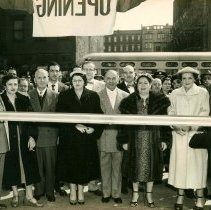 Image of B+W photo of Nathan Marcus, his wife and store staff posing in front of the ribbon at the Grand Opening of Marcus Jewelers, Hoboken, April 3, 1954. - Print, Photographic