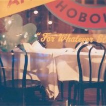 "Image of Color print ""Night Photography of Hoboken; Through the Storefront."" Photograph taken by Donna Clovis, no date, ca. 2002. - Print, Photographic"