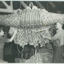 Image of Postcard: photo of two workers weaving rope using fids to make a bow fender, ca. 1952; published by Hudson Waterfront Museum, West New York, 1991. - Postcard