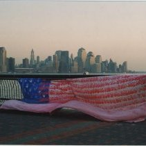 Image of Color photo of the Georgia Children's Memorial Flag as hung by Robert Guglielmetti at Pier A Park, Hoboken, ca. November, 2001. - Print, Photographic
