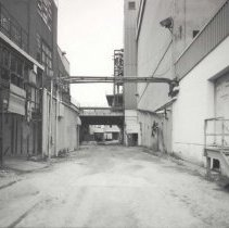 Image of Digital image of B+W photo of former Maxwell House Coffee plant exterior, looking north between Extraction Building & Storage Silos, Hoboken, 2003. - Print, Photographic