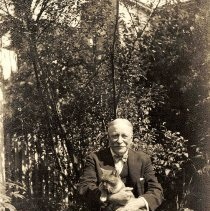 Image of B+W photo of of Richard Neumann of R. Neumann & Co. seated in a yard holding a cat, Hoboken?, no date, ca. 1920's. - Print, Photographic