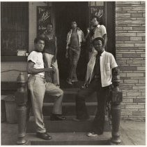 Image of B+W photo of a group of young men standing outside the entrance to The Astor, Hoboken, no date, [1976]. - Print, Photographic
