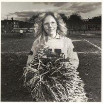 Image of B+W photo of Cynthia Lisa, a Hoboken High School cheerleader performing at a football game, JFK Stadium, Hoboken, no date, [1976]. - Print, Photographic