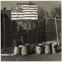 Image of B+W photo of a painted spirit of ''76' flag on wood mounted above a chain link fence, Hoboken, no date, [1976]. - Print, Photographic