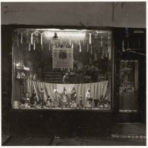 Image of B+W photo of a night view of the window of Botanica Santa Marta store, street number 302, street not named, Hoboken, no date, [1976]. - Print, Photographic