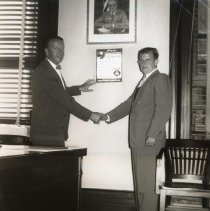 Image of Digital image of b+w photo of Mayor Fred DeSapio putting up first Civil Defense poster with Philip Morris manager, Hoboken, no date, ca. 1950-1952. - Print, Photographic