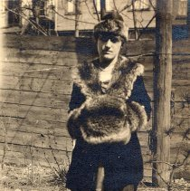 Image of Digital image of photo of a woman posed outdoors with fur trimmed coat and muff probably in a backyard, no place (Hoboken?), no date, ca 1915-1925. - Print, Photographic